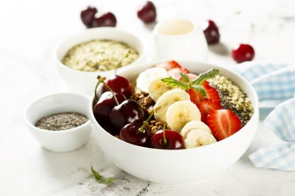 A bowl of hemp hearts with cherries, strawberries, and sliced bananas