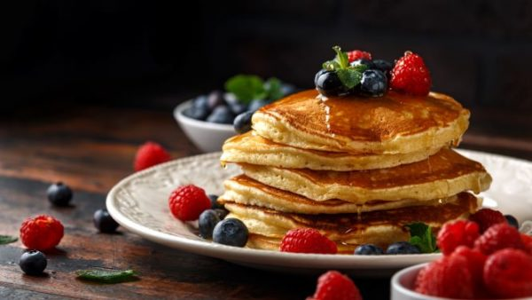 Pancakes topped with berries and organic yacon syrup