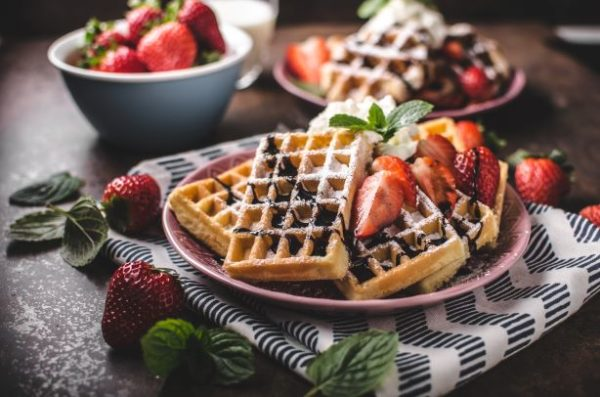 Plates of waffles topped with powdered sugar and sliced strawberries