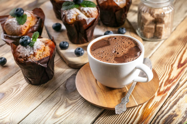Muffins with blueberries and a cup of hot chocolate on a wooden background